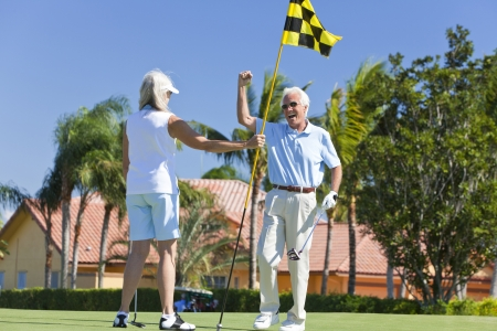 Happy senior man and woman couple together playing golf celebrating on a putting green together
