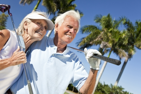 Happy senior man and woman couple together playing golf putting on a green together Imagens