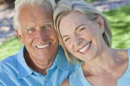 Happy senior man and woman couple sitting together outside in sunshine photo