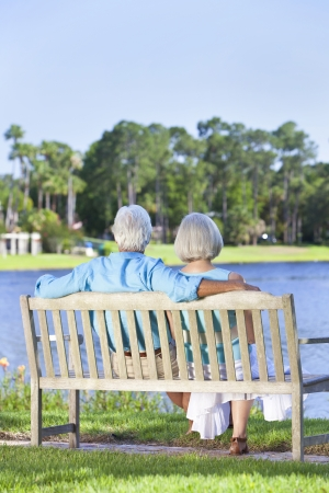 Rear view of a happy romantic senior couple sitting on a park bench looking at a blue lake photo