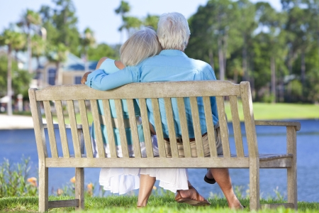 Rear view of a happy romantic senior couple sitting on a park bench embracing looking at a blue lake