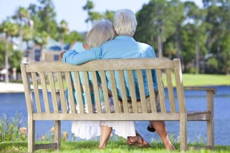 jubilados: Vista trasera de una pareja de ancianos feliz que se sienta en un banco del parque global mirando a un lago azul