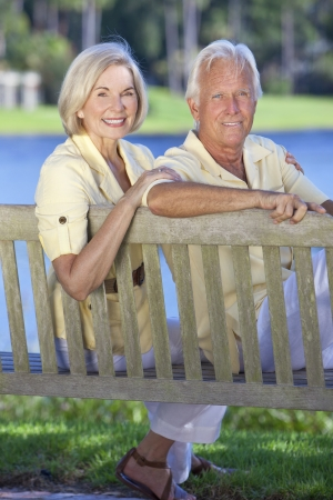 Happy romantic senior couple sitting on a park bench next to a blue lake Stock Photo - 19525356