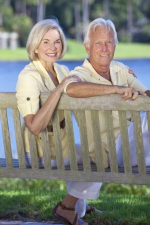 Happy romantic senior couple sitting on a park bench next to a blue lake Stock Photo - 19525356