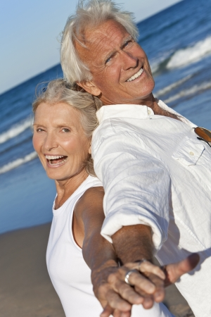 Happy senior man and woman couple back to back and holding hands on a deserted tropical beach with bright clear blue sky photo