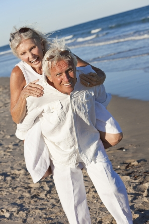 Happy senior man and woman couple playing piggy back and having fun on a deserted tropical beach photo