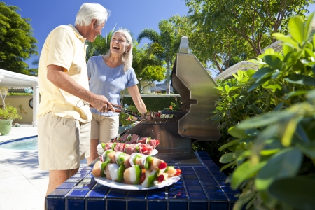 Happy senior man and woman couple outside cooking kebabs on a summer barbecue 免版税图像