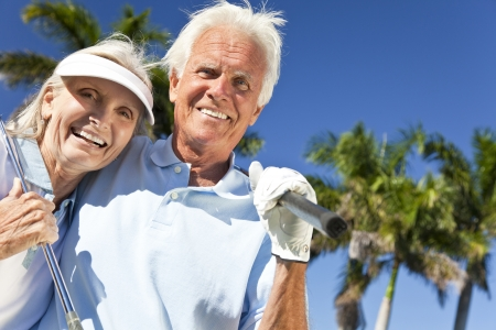 Happy senior man and woman couple together playing golf  Banco de Imagens
