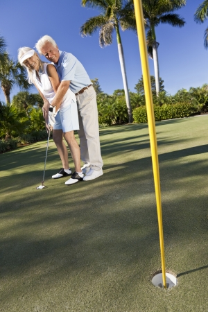 Happy senior man and woman couple together playing golf putting on a green together photo
