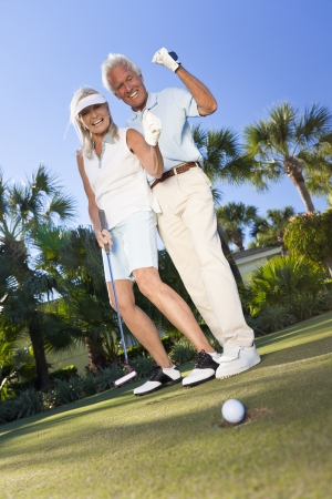 woman golf: Happy senior man and woman couple together playing golf and putting on a green, celebrating the ball going in the a whole, a successful shot