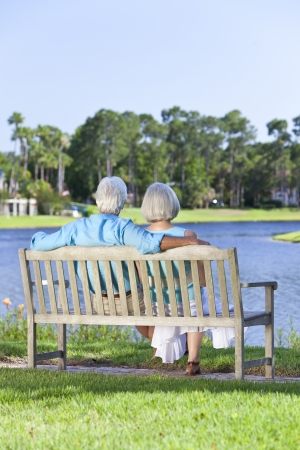 Rear view of a romantic senior couple sitting on a park bench looking at a blue lake Stock Photo - 19524519