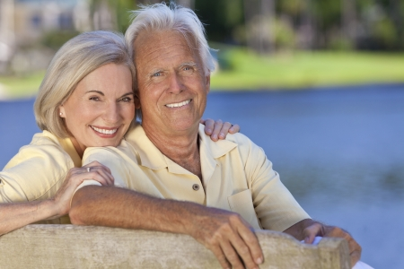 Happy smiling romantic senior man and woman couple sitting on a park bench embracing by a blue lake