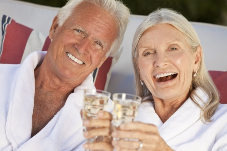 Happy senior man and woman couple at health spa in white bathrobes smiling and drinking champagne photo