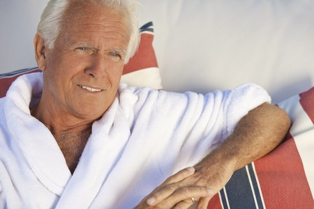 handsome old man: Portrait of a happy attractive handsome senior man in a white bathrobe sitting down outside smiling.
