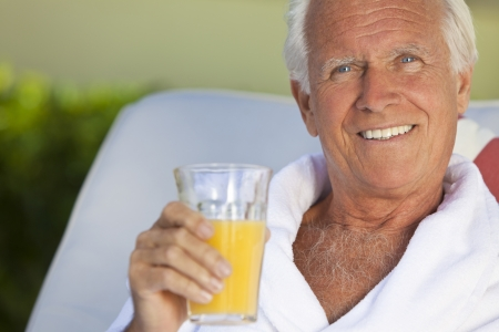 handsome old man: Portrait of a happy healthy handsome senior man in a white bathrobe sitting down outside smiling and drinking orange juice