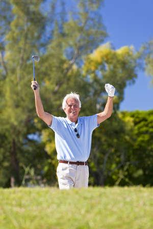 golfing: Happy senior man celebrating a successful shot playing golf