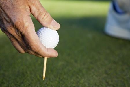 Senior man hand with golf ball and tee photo