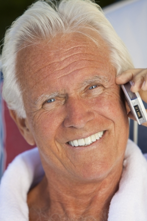 tanned: Portrait of a happy attractive handsome senior man in a white bathrobe sitting down outside smiling talking on his cell phone Stock Photo