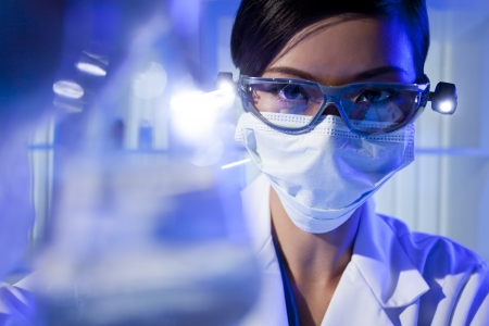 investigador cientifico: Un investigador m�dico o cient�fico femenino asi�tico chino o un m�dico mirando un frasco de l�quido transparente en un laboratorio. Foto de archivo