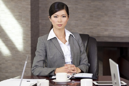 chairman: Beautiful Asian Chinese Woman or businesswoman sitting at a boardroom table