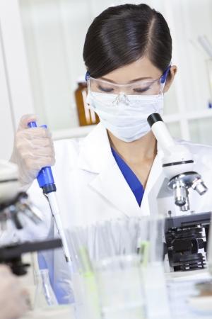 investigador cientifico: Un chino de Asia investigadora m�dica o cient�fica, o doctor con una pipeta y un microscopio en un laboratorio Foto de archivo