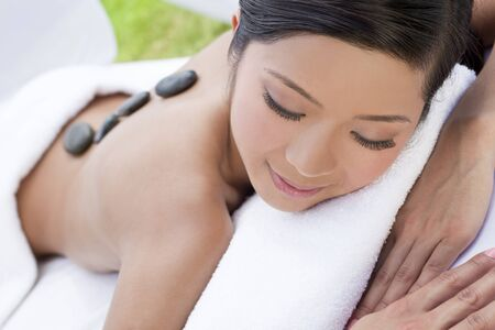 An Asian Chinese woman relaxing outside at a health spa while having a hot stone treatment or massage photo