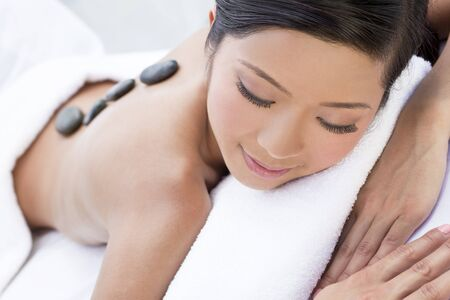 An Asian Chinese woman relaxing at a health spa while having a hot stone treatment or massage photo