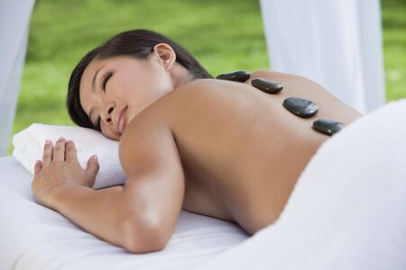 sensual massage: An Asian Chinese woman relaxing outside at a health spa while having a hot stone treatment or massage Stock Photo