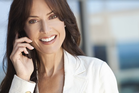 Outdoor portrait of a beautiful happy brunette woman or businesswoman in her thirties talking on her cell phone photo