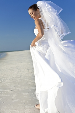 woman beach dress: A married woman bride in her wedding dress in sunshine on a beautiful tropical beach