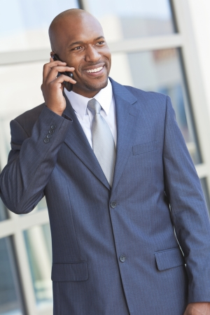 african businessman: Successful African American businessman or man talking on his cell phone in a modern city