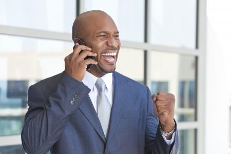 fist pump: Successful African American businessman or man in a suit in a modern city talking on his cell phone celebrating success Stock Photo