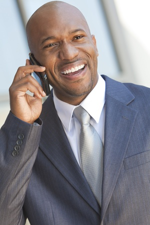 Successful African American businessman or man in a suit in a modern city talking on his cell phone photo