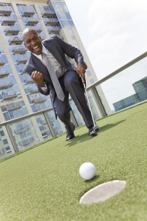 Successful African American businessman or man in a suit playing golf on a corporate putting green on roof of a skyscraper office building photo