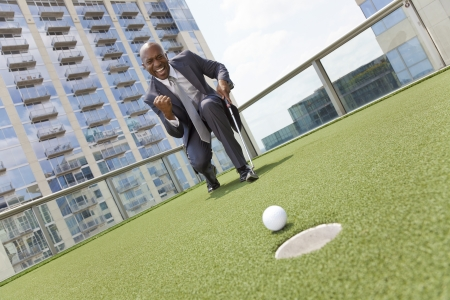 fist pump: Successful African American businessman or man in a suit playing golf on a corporate putting green on roof of a skyscraper office building
