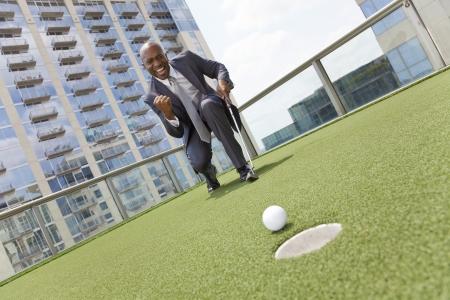 Succesvolle Afrikaanse Amerikaanse zakenman of man in een pak golfen op een corporate putting green op het dak van een wolkenkrabber kantoorgebouw Stockfoto
