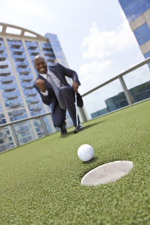 Successful African American businessman or man in a suit playing golf on a corporate putting green on roof of a skyscraper office building, The focus in this image is on the ball, see other images in our portfolio where the focus is on the businessman. photo