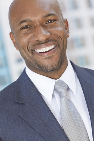 Successful and happy smiling African American businessman or man arms in a modern city photo