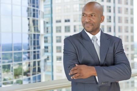 hombre calvo: Exitoso hombre de negocios afroamericanos o los brazos cruzados hombre en un traje en una ciudad moderna