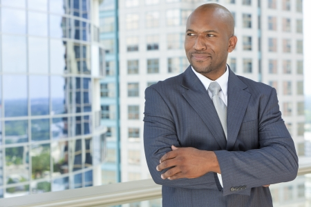 Successful African American businessman or man arms folded in a suit in a modern city photo