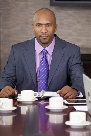 An African American businessman, chairman or man in a business suit, sitting at an office boardroom table  photo
