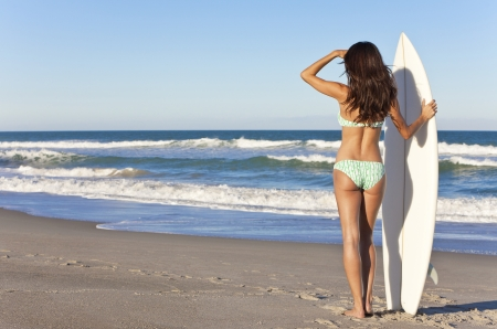 surf board: Rear view of sexy beautiful young woman surfer girl in bikini with white surfboard at a beach