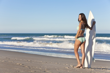 Beautiful sexy young woman surfer girl in bikini with white surfboard at a beach photo
