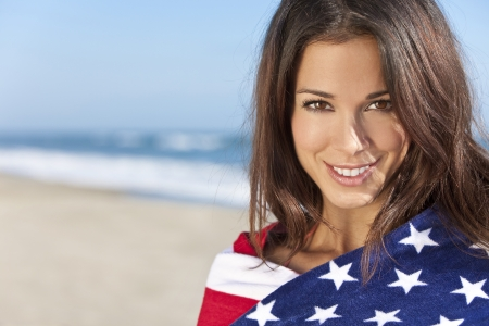 Beautiful young womn wrapped in American flag towel on a sunny beach photo
