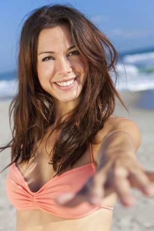 hands out: Beautiful young women or girl in bikini on a sunny beach smiling and reaching hand to the camera Stock Photo