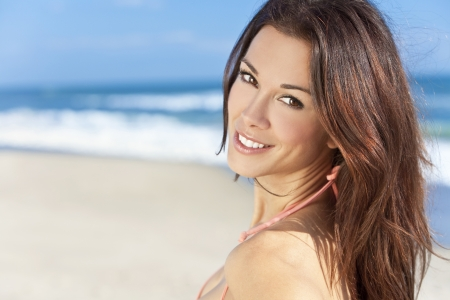 dental smile: Stunningly beautiful young brunette woman in sunshine on a beach and wearing a bikini