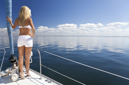 boat crew: Rear view of beautiful young woman standing on the bow of a sail boat on a tranquil calm blue sea Stock Photo