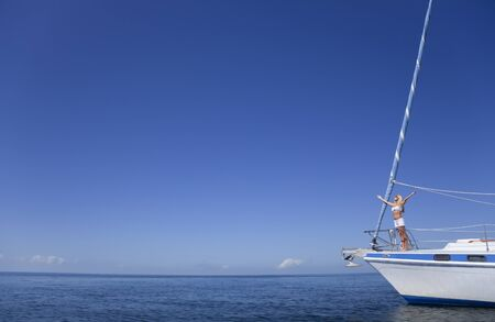 Beautiful young woman standing arms raised on the bow of a sail boat on a tranquil calm blue sea photo