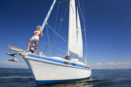 sailboat: A beautiful young woman in shorts and a bikini standing on the front of a sail boat on a calm blue sea Stock Photo