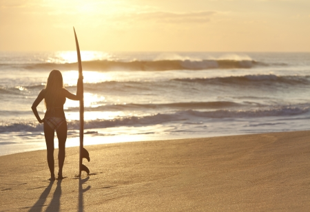 일출 또는 일몰에 해변에서 surfbord 비키니에서 아름 다운 젊은 여자 서퍼 소녀의 후면보기